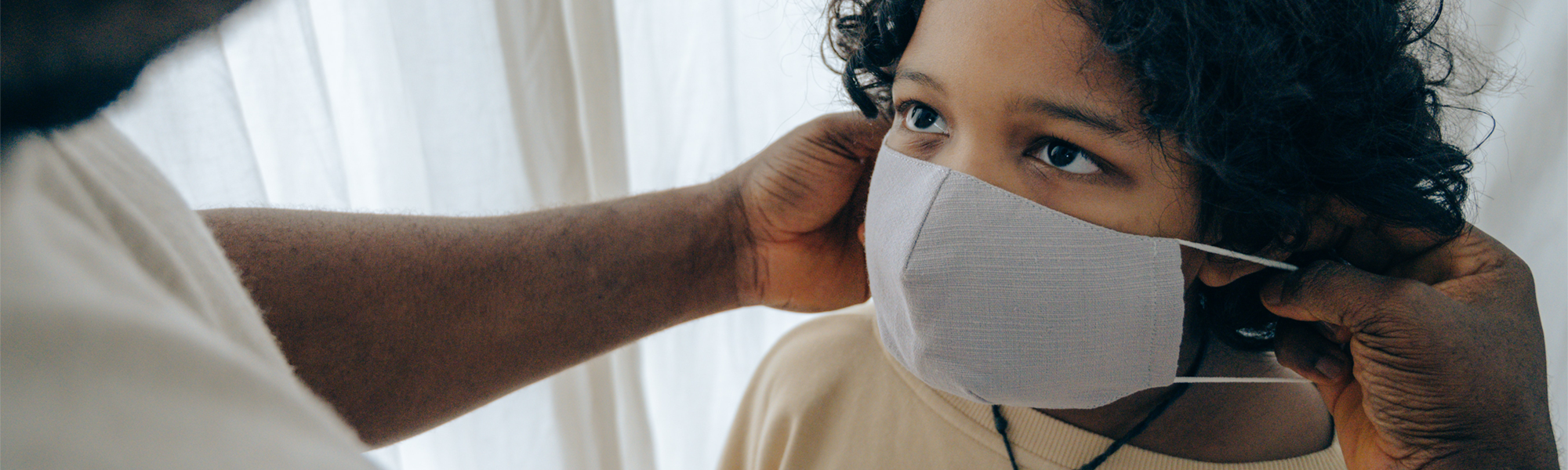 Photo of a care giver putting a mask on a child