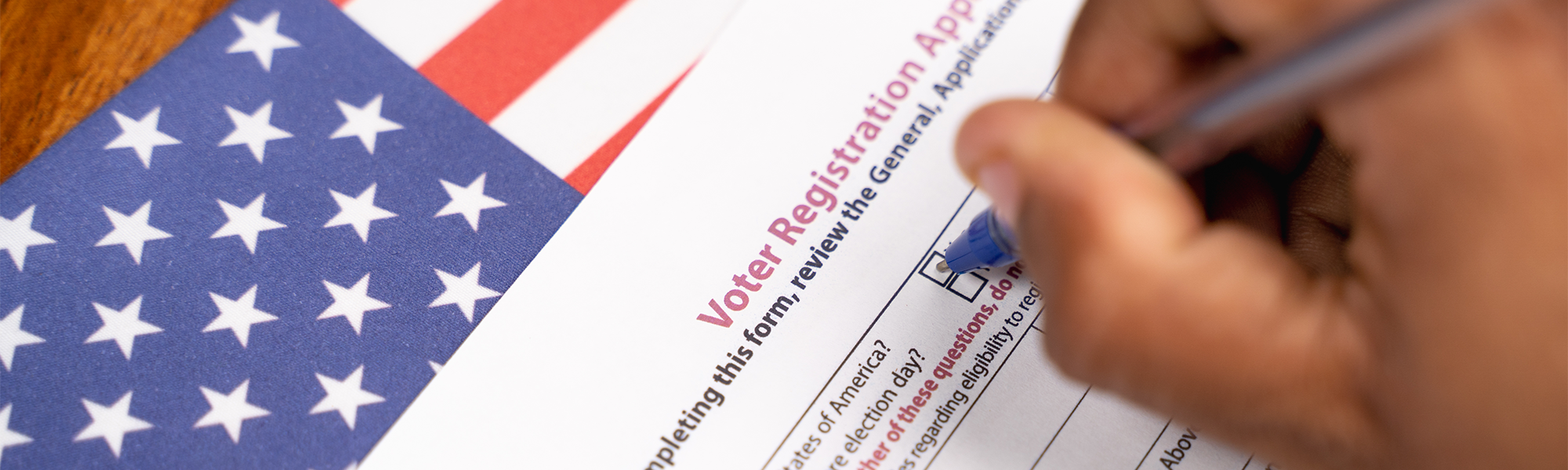 a hand filling out a voter registration form