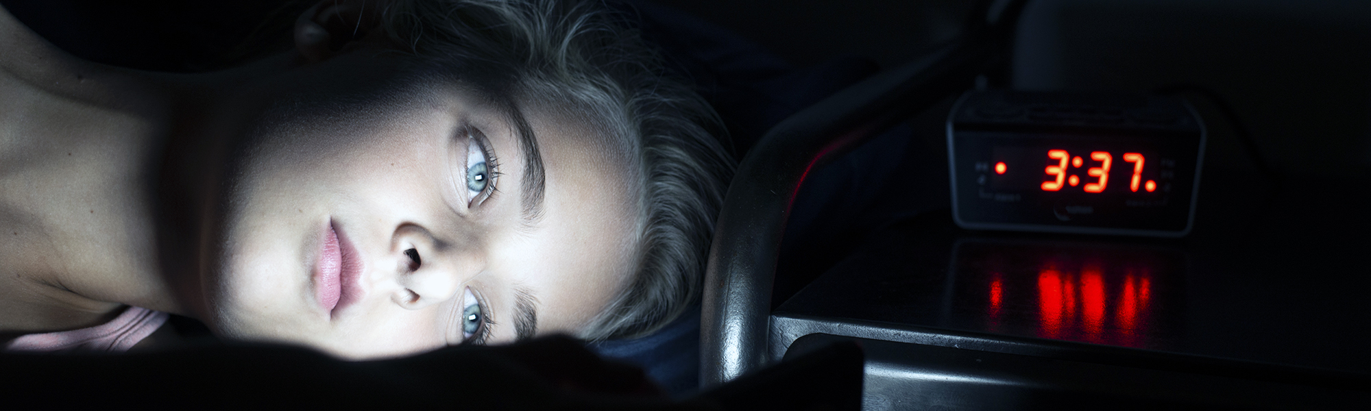 Young girl using mobile phone in bed at midnight, can't sleep