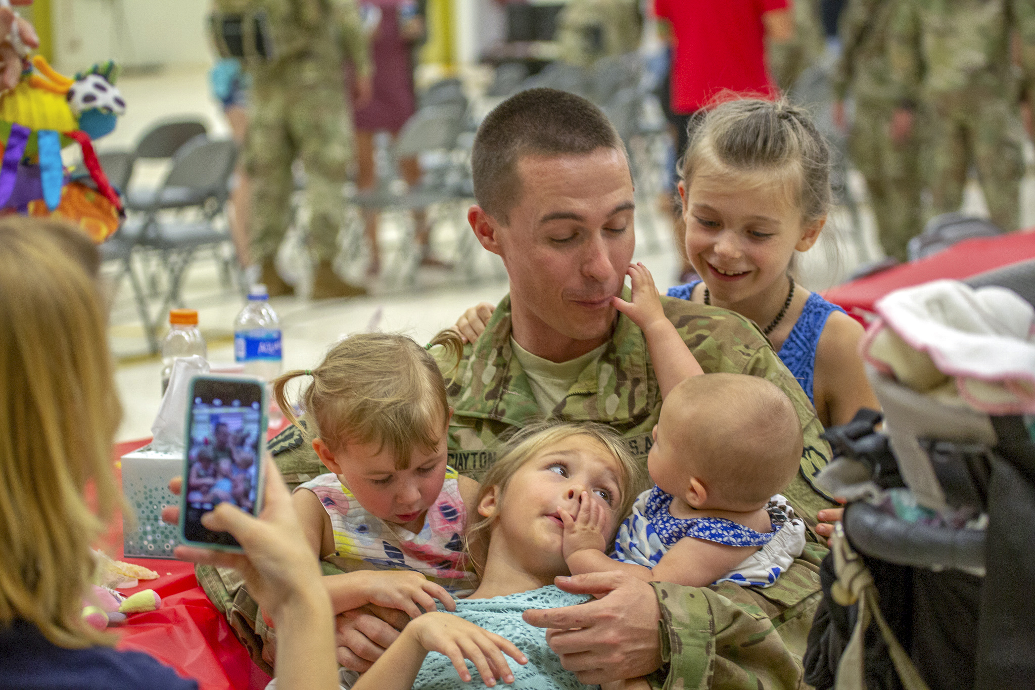 A soldier of Bravo Company 'Hillclimbers', 3-25 Aviation Regiment embraces his family at a ceremony honoring the troops prior to their deployment at Wheeler Army Airfield Jun. 5. The 'Hillclimbers' will support Operation Freedom's Sentinel and Operation Resolute Support in the CENTCOM area of responsibility for nine months.